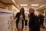 Honors Scholar Eliana Iller explains her poster to Keith Mattingly, Dean of the College of Arts and Sciences by Andrews University