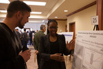 "Honors Scholar Allegra Stennett (right) explains her poster ""The Association between Open Market Operations and the S&P 500 Index from 2008-2010"""