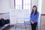 "Honors Scholar Christine Lee poses beside her poster ""hcnABC Operon Transcription of Pseudomonas putida under Varying Iron and Oxygen Concentrations and Culture Age"""