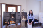 Honors Scholar Lynda Lee poses beside her poster and artwork by Andrews University